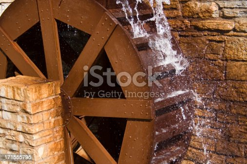 A wooden water wheel or watermill turbine milling, grinding, turning, and generating power, perhaps as a traditional alternative energy source. Positioned against the stone wall of a cottage building exterior, located in St. Paul, Minnesota, USA.