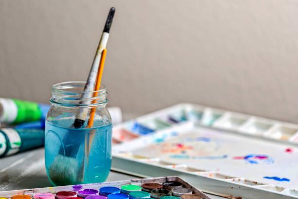 aquarell und acrylfarbe - palette und farbe pinsel im wasser. - glasmalerei stock-fotos und bilder