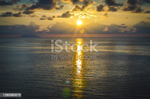 istock Watercolor drawing of Aerial view of beautiful amazing sea sunset, seascape and endless horizon with color dramatic sky with clouds and volcano hill mountain island Stromboli, Tropea, Calabria, Italy 1283380075