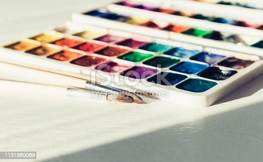 Watercolor paint and brushes well used on white wooden table with copy space for text