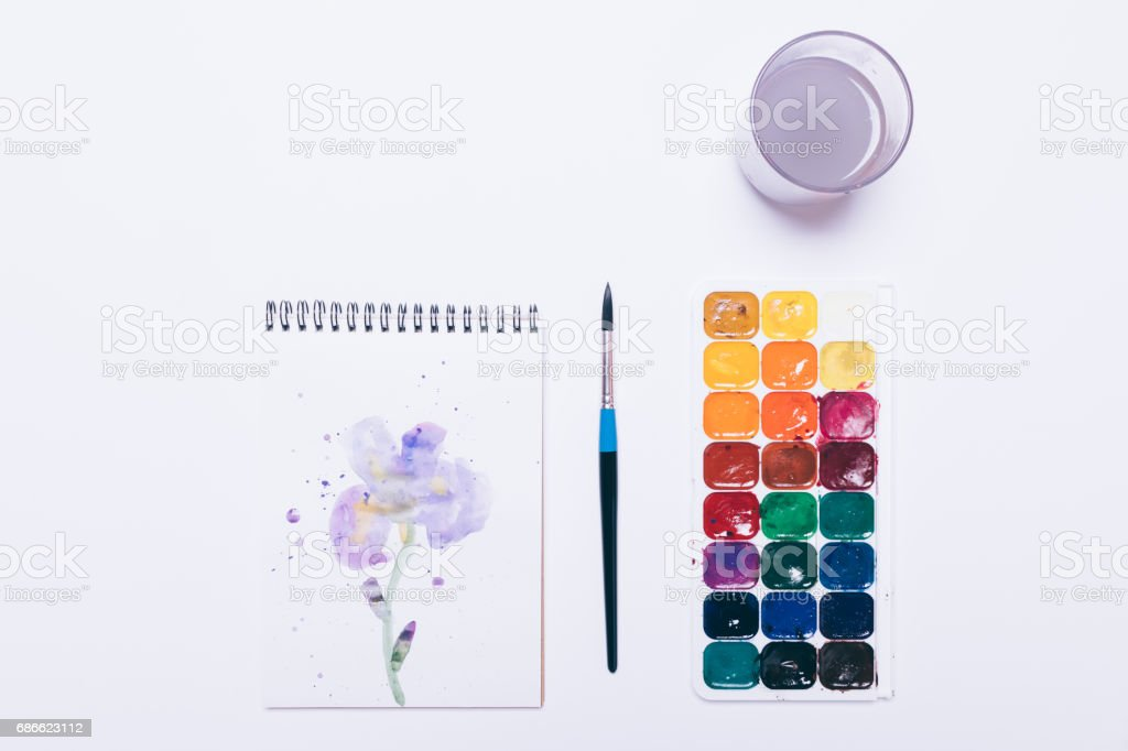 Watercolor paint, brush, painted blue flower and a glass with water on a white background photo libre de droits