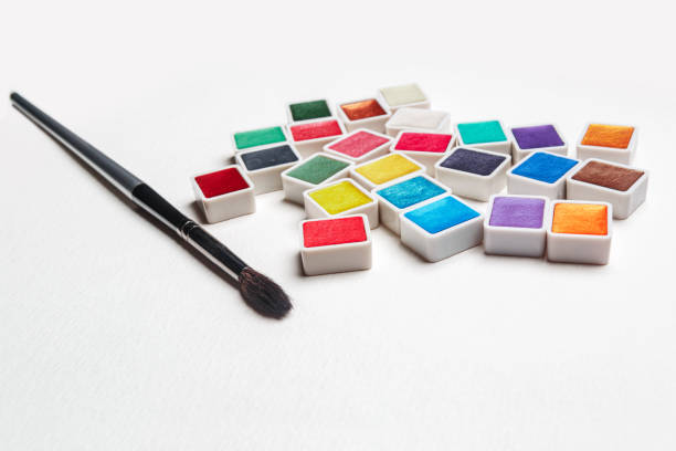 Watercolor Paint in Pans and paintbrush, clean and new isolated on white background. Vibrant pearlescent colors with copy space. stock photo