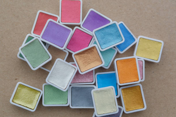 Watercolor Paint in Pans, clean and new isolated on brown background. Vibrant pearlescent colors with copy space. stock photo