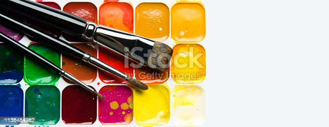 istock Watercolor paintbox and paintbrushes panorama on white 1138484982