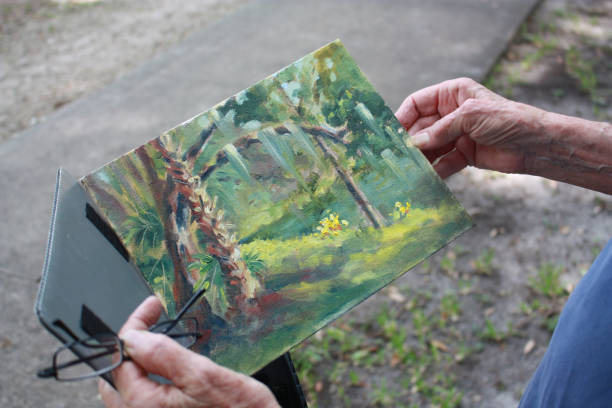 Watercolor painting held by Senior woman's hands stock photo