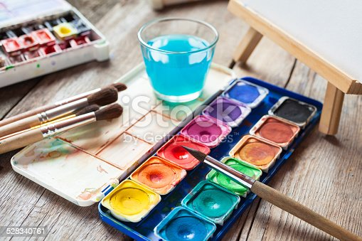 istock Watercolor paints, art brushes, glass of water and easel. 528340761