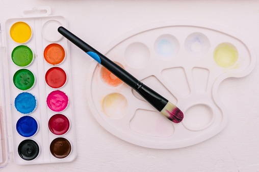 577949148 istock photo Watercolor paints, brush and palette on a white background. Tools for creativity and learning. Artist's kit 1263450181