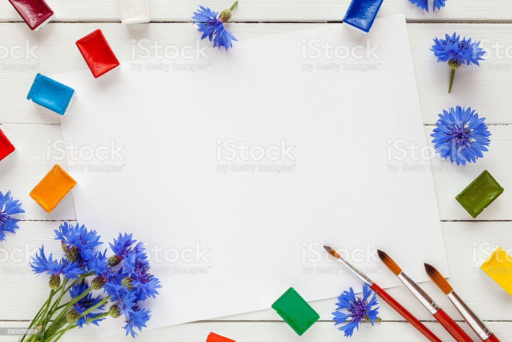Watercolor paints, brushes, cornflower and white paper sheet stock photo
