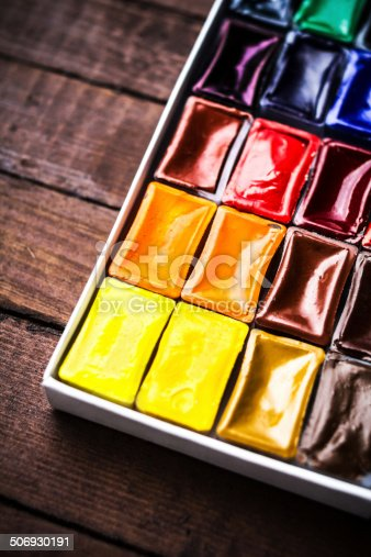 istock Watercolor paints on vintage wooden background close up. Art 506930191