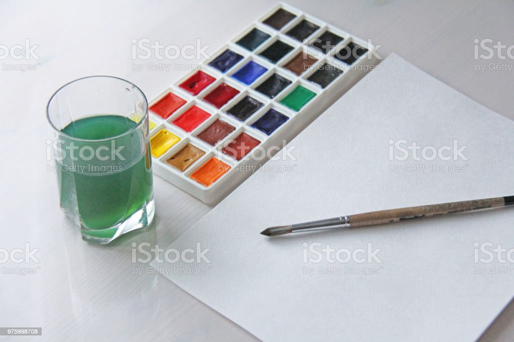 Watercolors, brushes, white sheet of paper and a glass of water for drawing. Hobbies and creativity stock photo