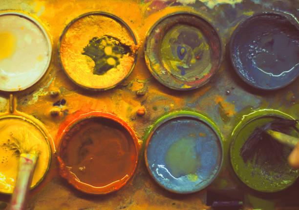 aquarelle malbox nahaufnahme, während zwei pinsel tauchen in farbzyklen. weicher fokuseffekt. - dip gefärbt stock-fotos und bilder