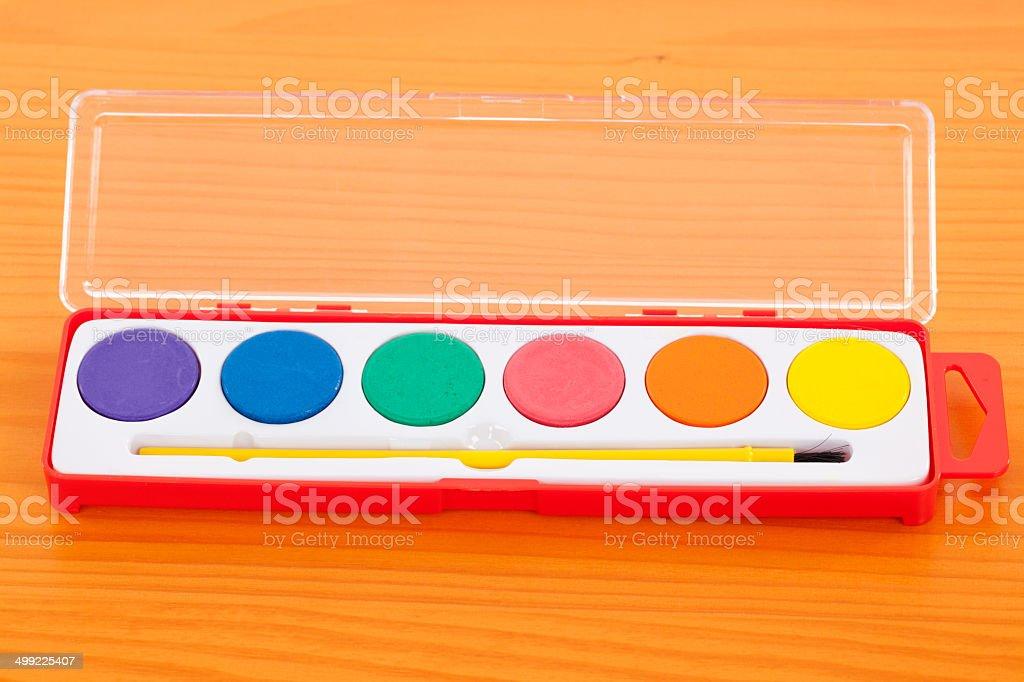 Watercolor paint set on a wooden desk.