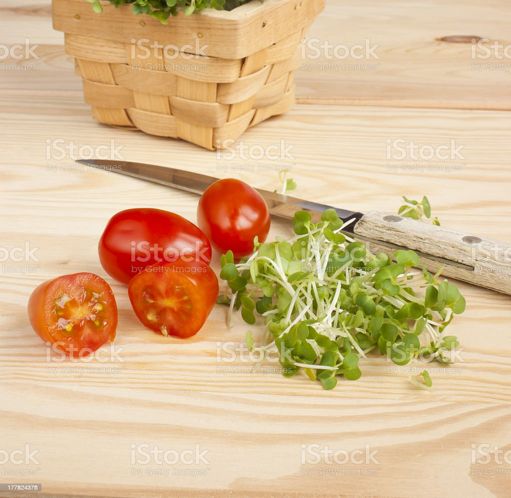 Watercress, tomatoes, knife on wooden table royalty-free stock photo