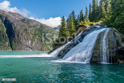 A waterfall cascades across smooth rock into the Tracy Arm Fjord in Alaska.