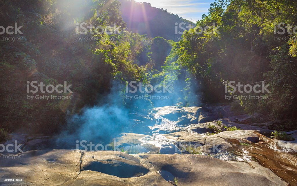Waterfall among forest in sunlight stock photo