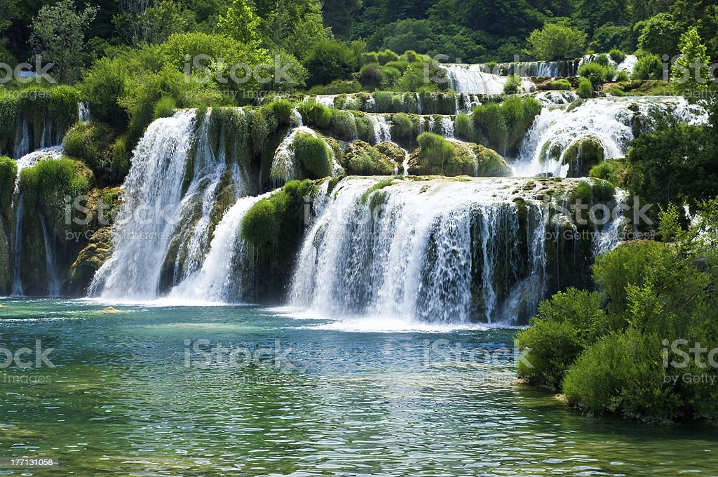 Waterfall among trees and moss covered rocks stock photo