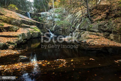 Blurred, misty water of a waterfall at Enders State Park in Granby, Connecticut, with reflections of the falls and autumn leaves in the dark water.