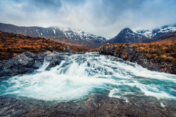 Waterfall and mountain at Fairy Pool in Isle of Skye, Scotland Waterfall and mountain at Fairy Pool in Isle of Skye, Scotland isle of skye stock pictures, royalty-free photos & images