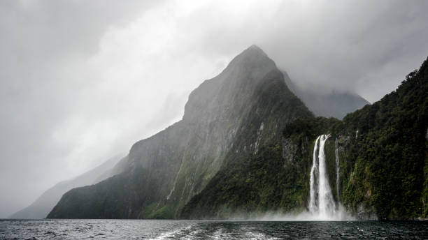 Waterfall and mountain peak in Milford Sound on a rainy day stock photo