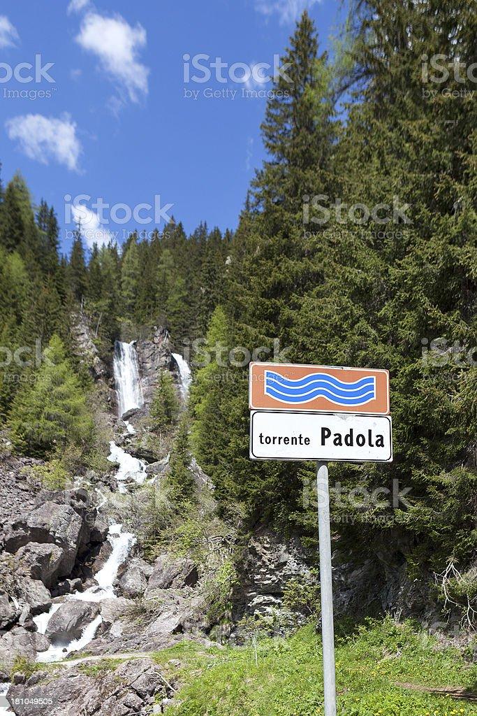 Waterfall and road sign, Torrente Padola, Veneto royalty-free stock photo