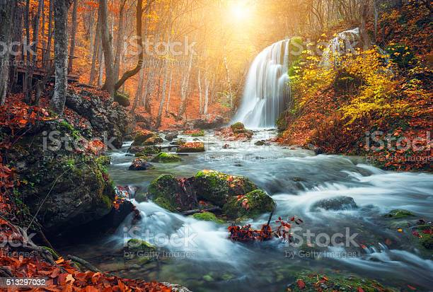 Photo of Waterfall at mountain river in autumn forest at sunset.