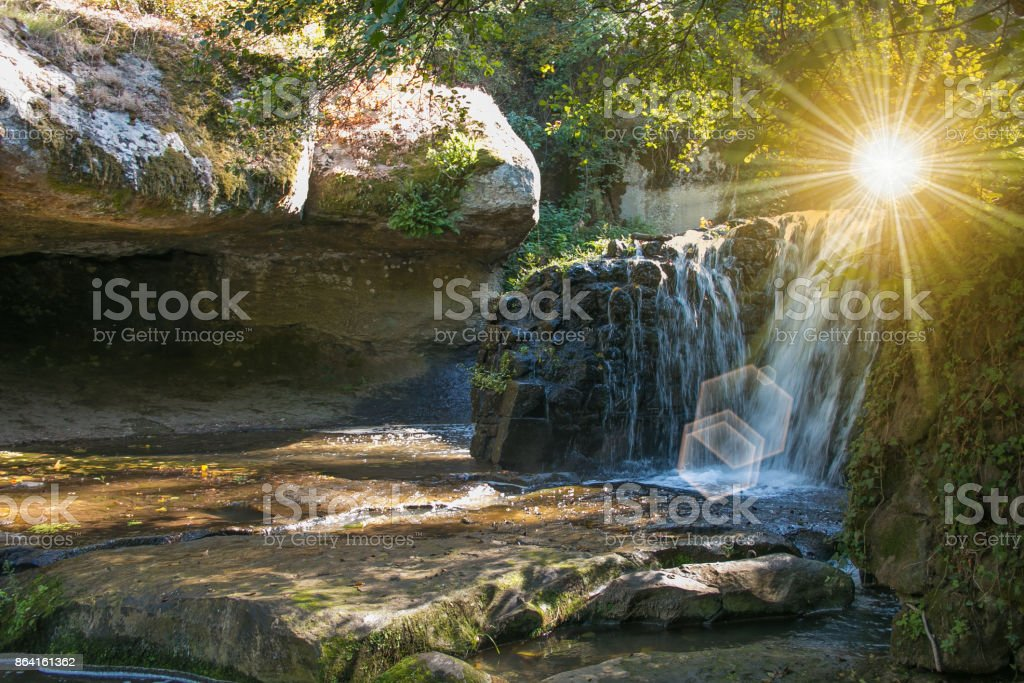 Waterfall at mountain river in colorful autumn forest with red and orange leaves at sunset royalty-free stock photo