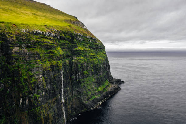 Waterfall coming out of cliffs above ocean. Gjogv, Faroe Islands. stock photo