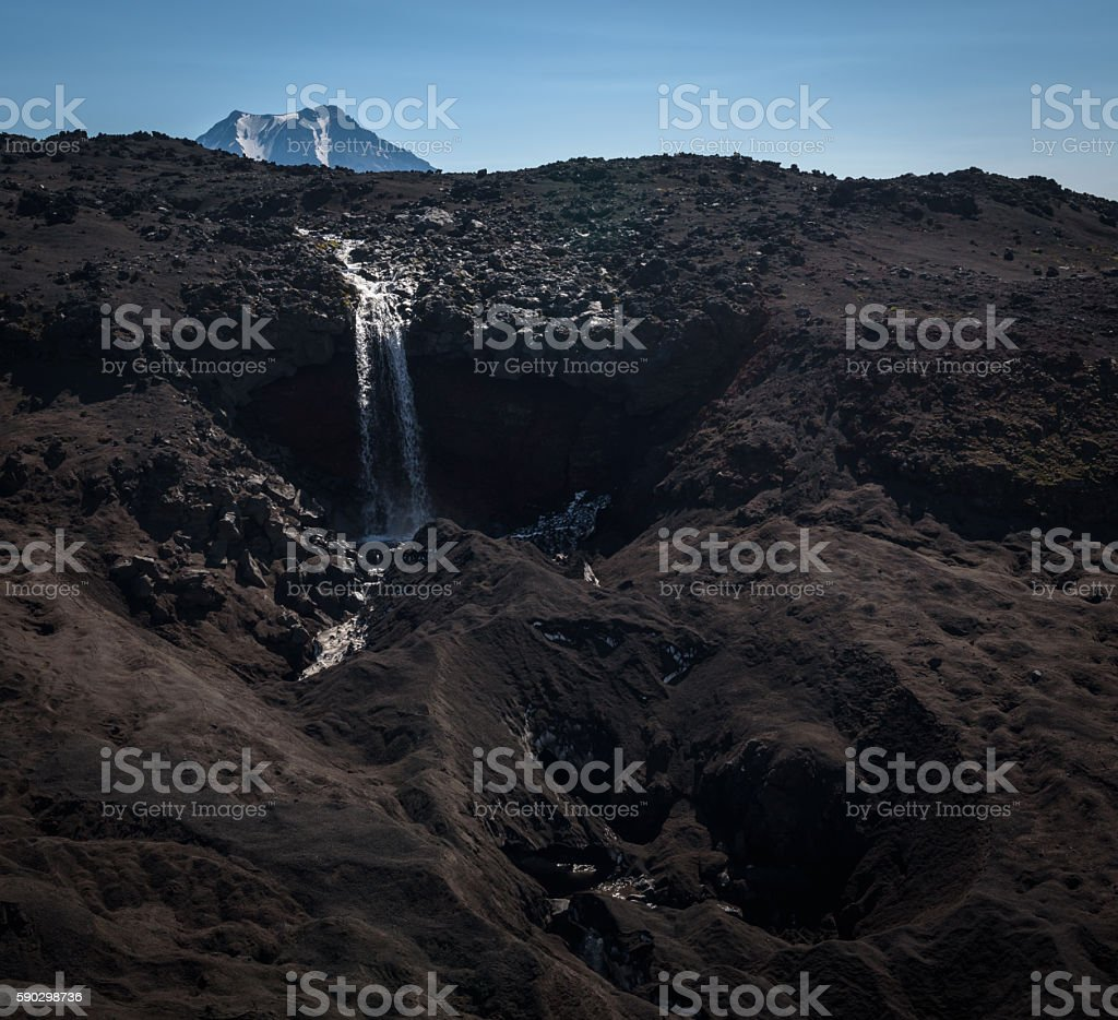 Waterfall falling from the glacier of Tolbachik Volcano royaltyfri bildbanksbilder