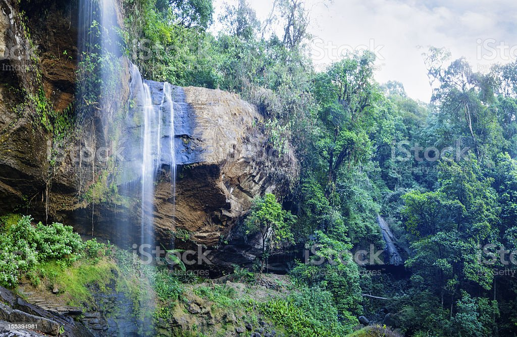 Waterfall falling over cliff in rainforest royalty-free stock photo