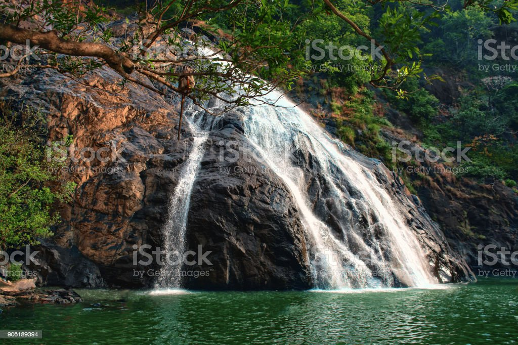 waterfall flows through the rocks and flows into the lake stock photo