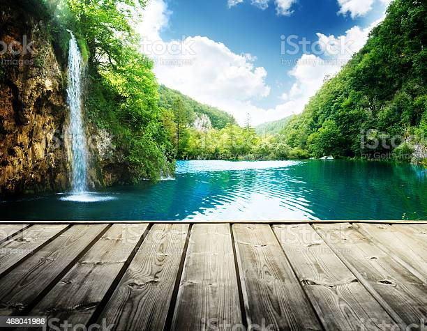 Photo of waterfall in deep forest of croatia and wood pier