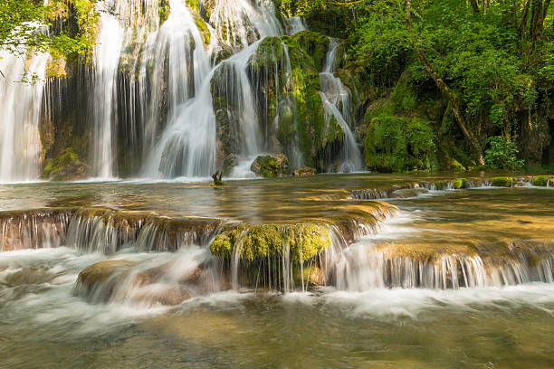 Waterfall in France Waterfall in French Jura Mountains: Cascade of Tuff (la cascade de tuf) near Arbois. - Long exposure with motion blur. tuff stock pictures, royalty-free photos & images