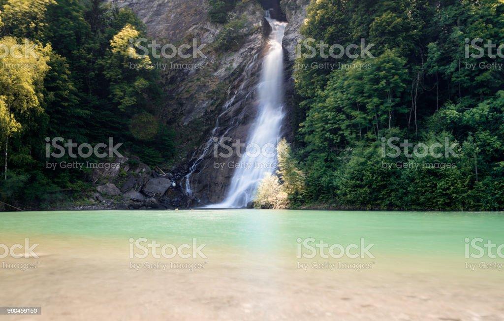 Wasserfall inmitten der Waldlandschaft in einem bunten Türkis und braun Teich kaskadieren – Foto