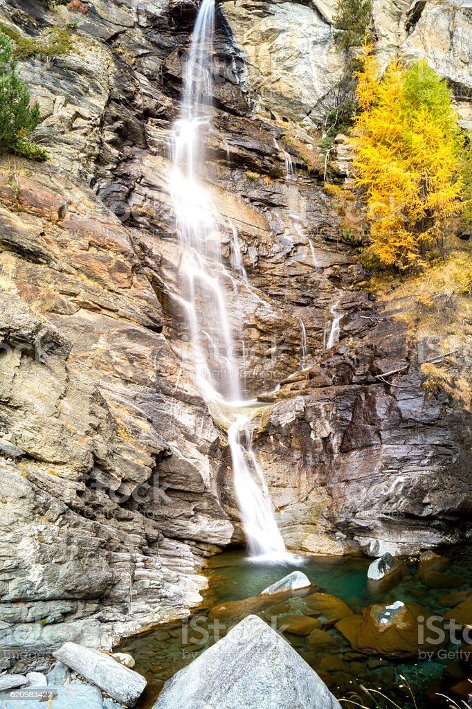 waterfall in the mountains and the autumnal trees, long exposure foto royalty-free
