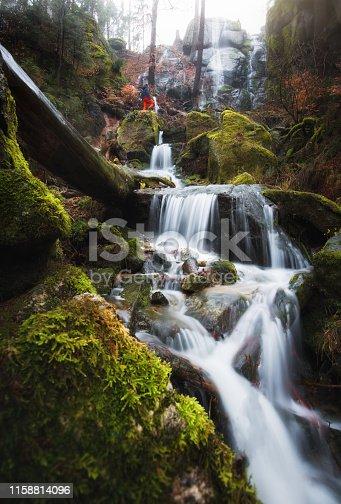 Wasserfall Langzeitbelcihtung mit Person. Grün, Felsen und Moos