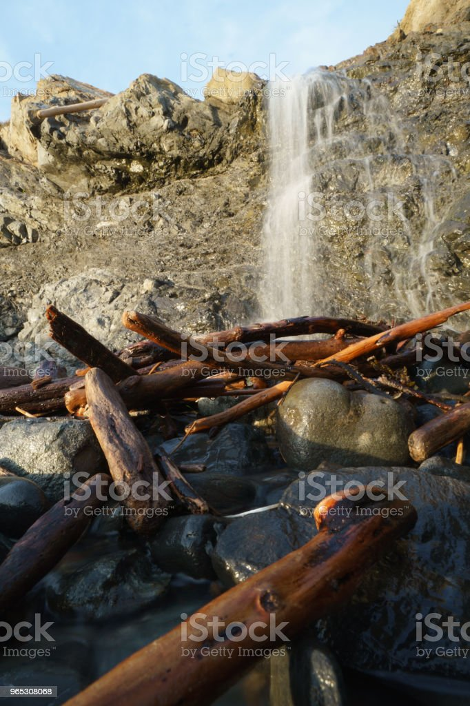 waterfall over cliff onto drift wood royalty-free stock photo