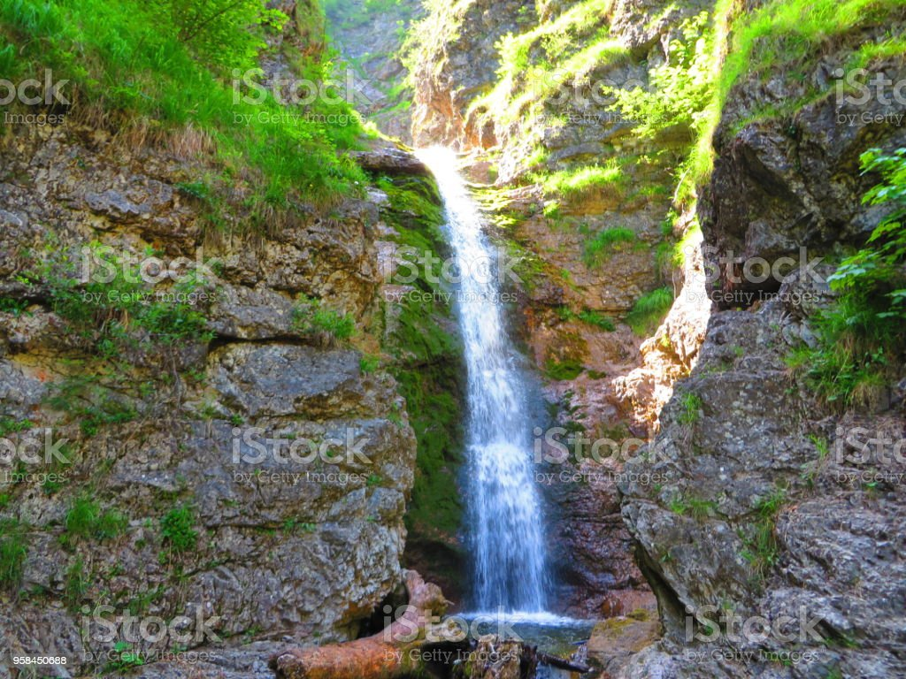 Waterfall over grass and rocks stock photo