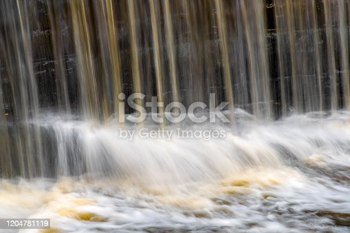 istock Waterfall over Weir, Tree Branch Poised To Go Over The Edge 1204781119