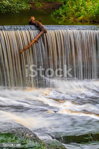 istock Waterfall over Weir, Tree Branch Poised To Go Over The Edge 1204781166