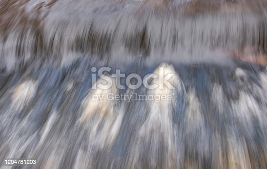 istock Waterfall over Weir, Tree Branch Poised To Go Over The Edge 1204781203