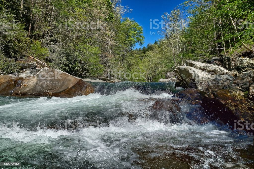 Waterfall & Rapids with pinetrees, rocks and blue sky stock photo