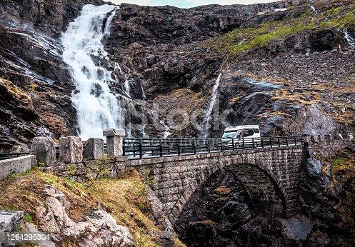 waterfall, stone bridge and camper on troll road in Norway
