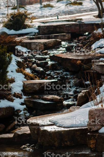 Photo of Waterfall trickling down some stones on a winter day