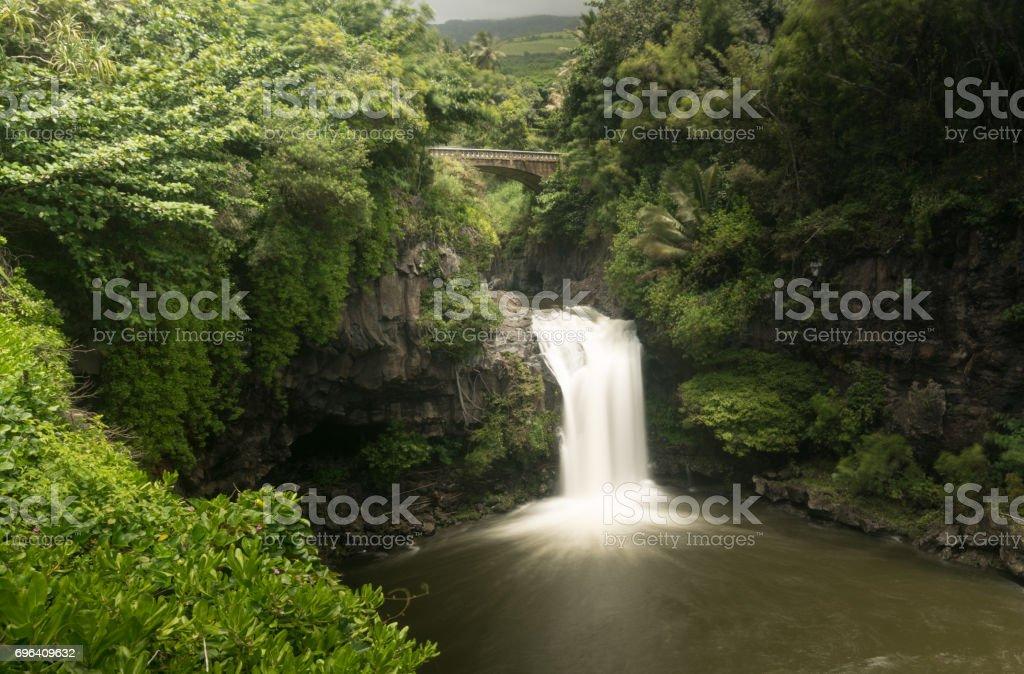Waterfall under road bridge at Seven Sacred Pools Maui stock photo