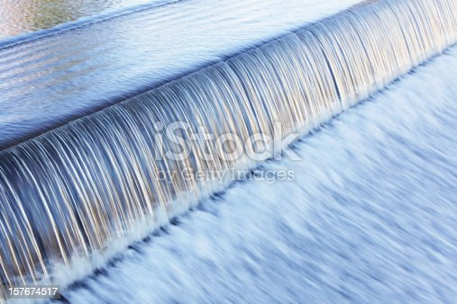 Water flows over a man-made waterfall at the edge of a Lake Placid, New York municipal river dam in a rushing, streaking transition from smooth, rippled calm into frantic, chaotic blur.