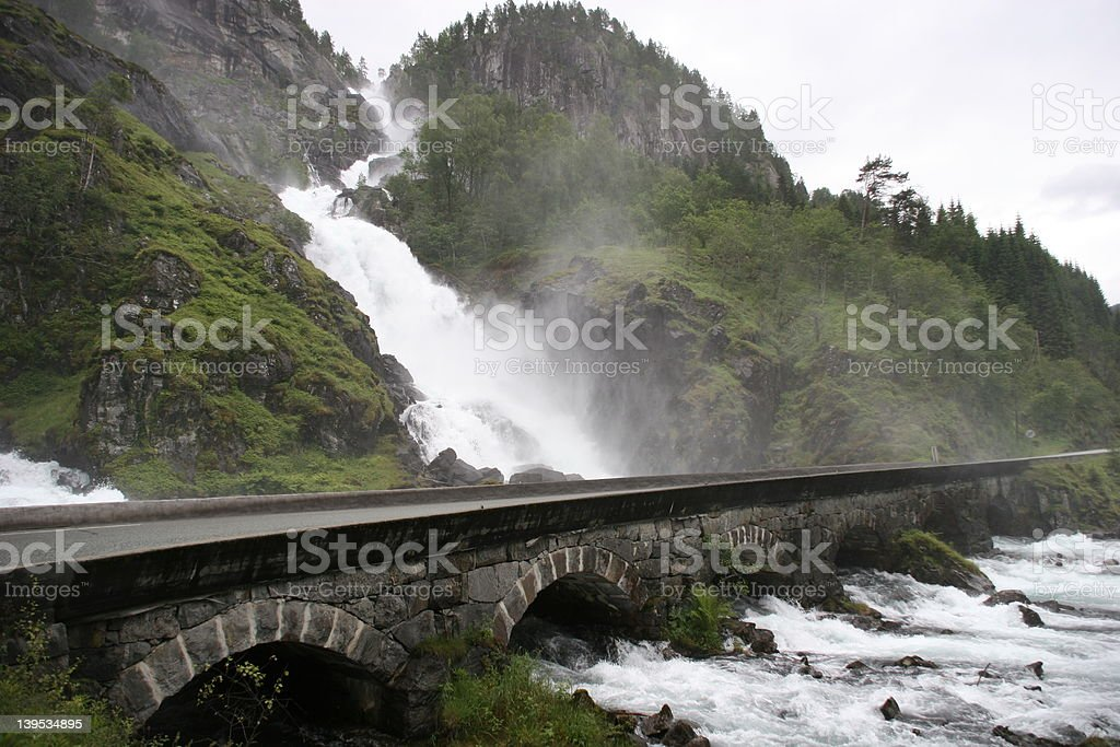 Waterfall with road Waterfall that flows underneath a road. Animals In The Wild Stock Photo