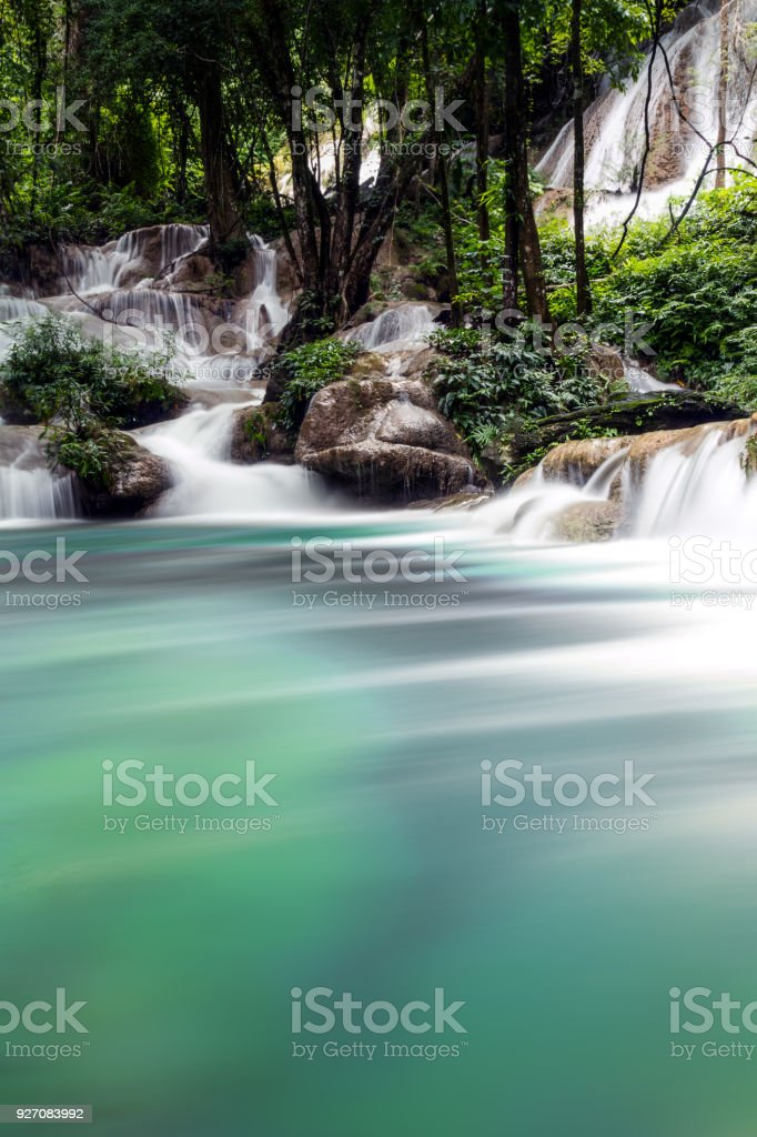 Waterfall with teal water, stone and forest. stock photo
