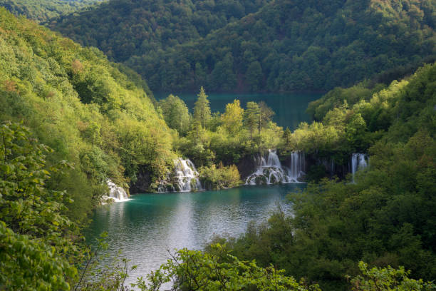 Waterfalls and lakes among green mountains Waterfalls and lakes among lush foliage. Scene in Plitvice Lakes National Park. côte d'ivoire stock pictures, royalty-free photos & images