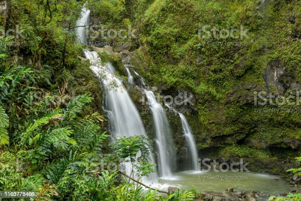 Photo of Waterfalls in Rain-forest - A close-up view of a multi-tiered waterfall inside of a dense rain-forest at side of the Road to Hana Highway on a rainy afternoon, Maui, Hawaii, USA.