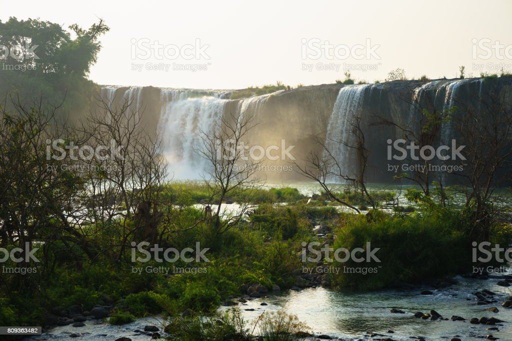 Waterfalls in the morning with dry trees on foreground stock photo